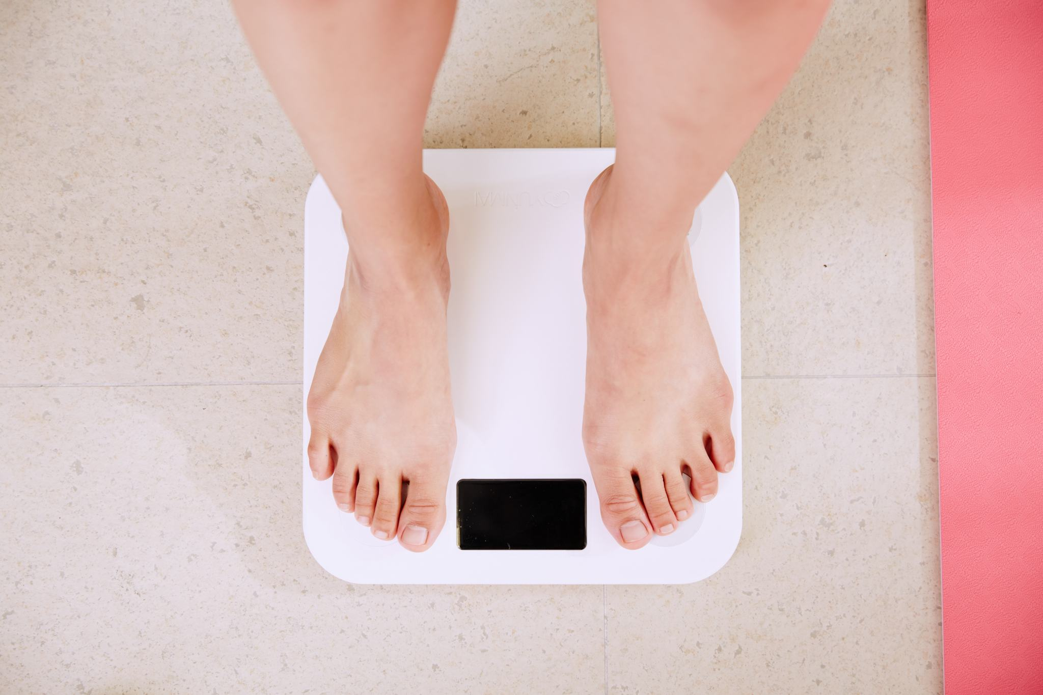woman standing on scale too stressed to lose weight