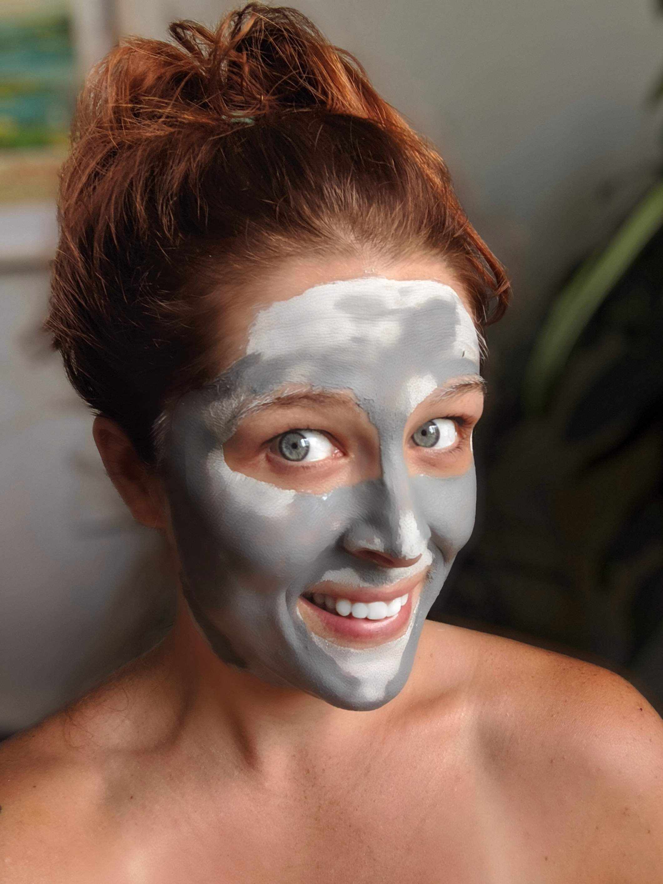 charcoal clay diy face mask on smiling woman's face